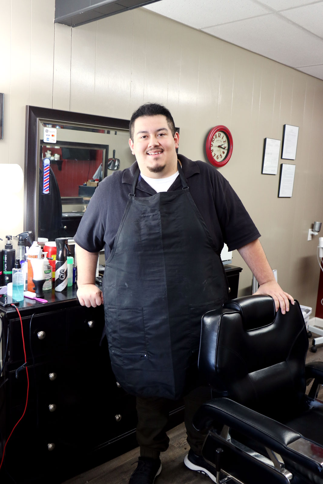 Ryelee Baros stands at his chair at His and Hers Salon.